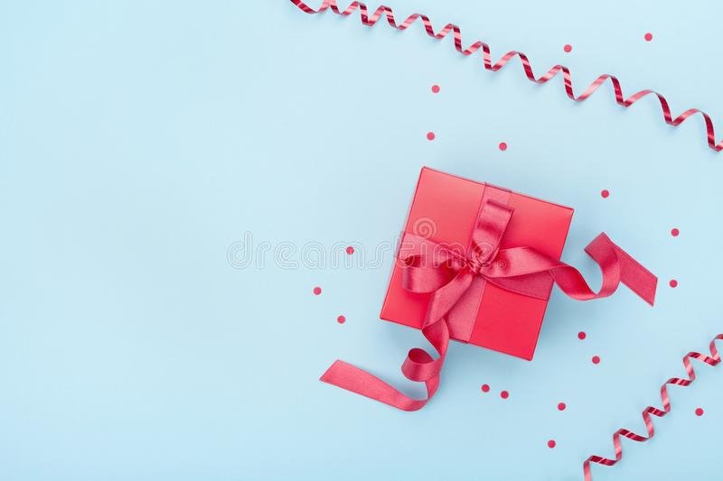 Minimalistic composition with red gift box, serpentine and confetti on blue background top view. Valentines day greeting card. stock image