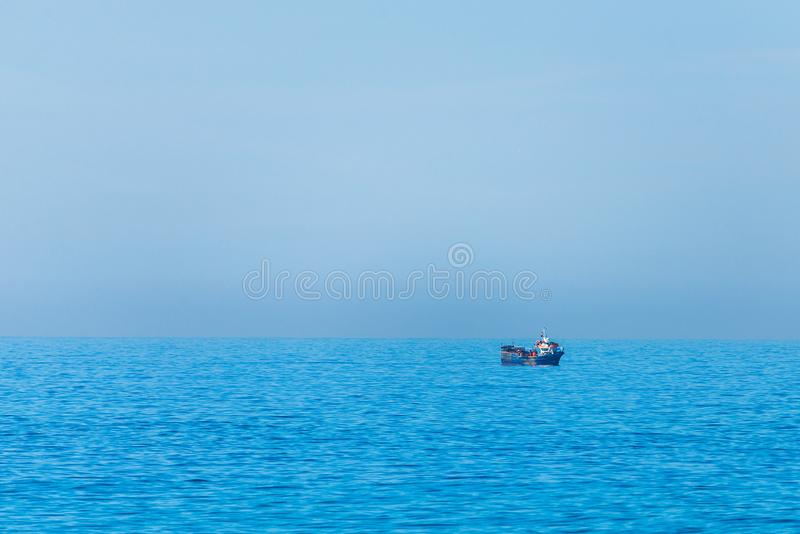 Minimalistic image of the sea with a fishing boat. Blue sea water and clear sky royalty free stock image