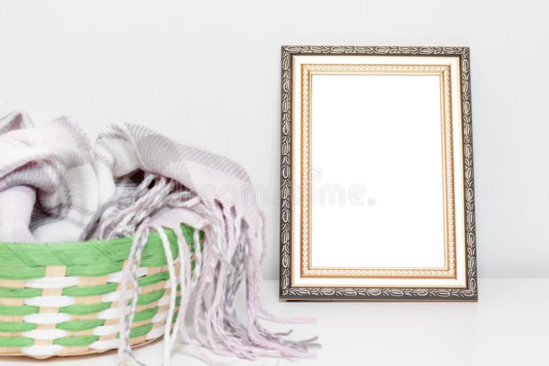 Minimalistic interior design with photo frame and a basket with warm woolen clothes on a desk royalty free stock photo