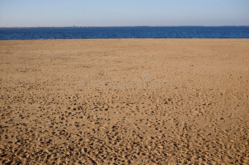 Minimalistic landscape empty sand beach and deep blue water in sunny day in autumn stock photos