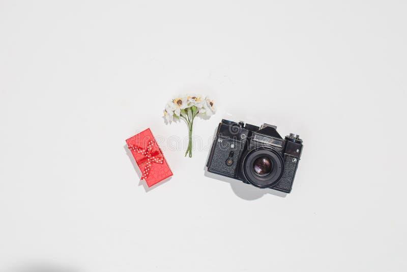 Minimalistic mieszkania nieatutowy skład z retro kamerą, czerwony prezenta pudełko i wiosny pole, kwitniemy na białym tle modny zdjęcia royalty free