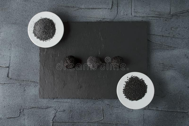Minimalistic sweets without sugar. Minimalistic natural raw sweets without sugar on black stone board. top view with copy space stock images