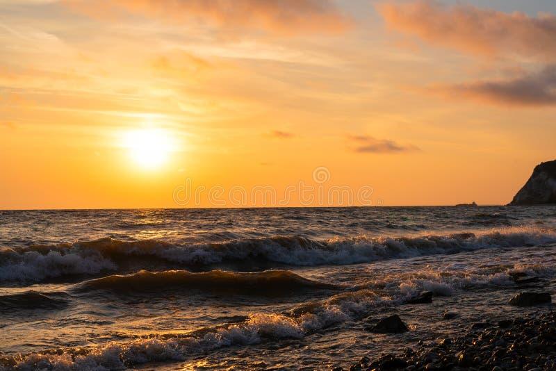 Minimalistic oranje zonsopgang over de oceaan met golven dichtbij de kust stock afbeeldingen