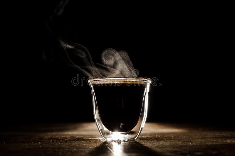 Minimalistic photo of glass mug with coffee. And steam from it located on the wooden table royalty free stock photography
