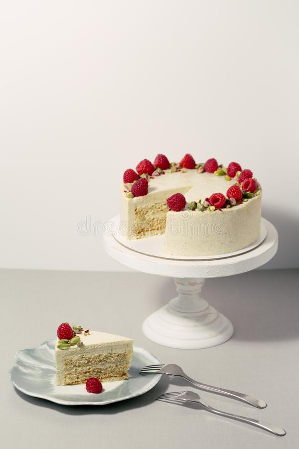 Minimalistic pistachio cake with raspberries. A piece of cake on the dish royalty free stock image