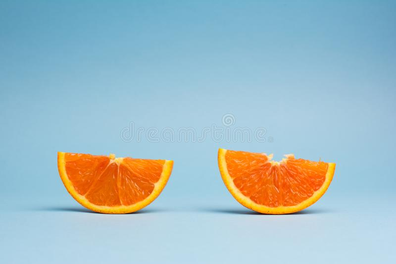 Minimalistic pop art color concept: two slices of orange fruit on blue background. Two slices of orange fruit on blue background, minimalistic pop art color royalty free stock photo