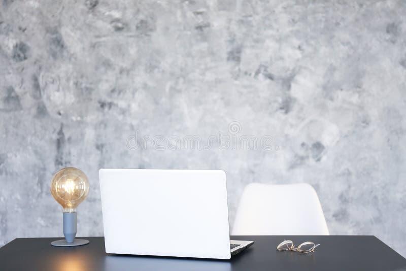 Minimalistic sammans?ttning av arbetsplatsen med b?rbara datorn och brevpapper royaltyfria foton