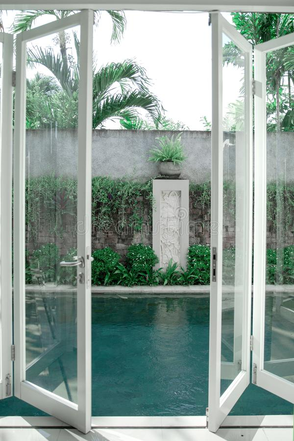 Minimalistic scandinavian interior of open glass door to swimming pool. And tropical plants. Bali style interior royalty free stock photography