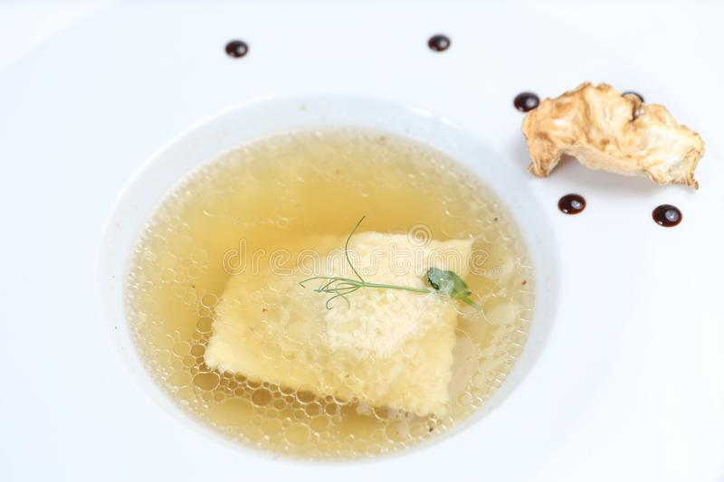 Minimalistic serving of food, white transparent chicken broth in a plate of rice, cheese and dumplings royalty free stock photos