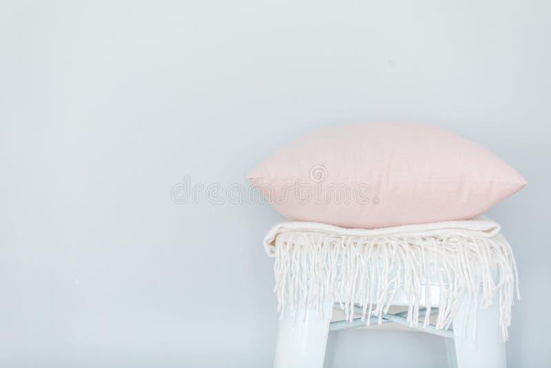 Minimalistic skandinavian beeld van een lichtrose hoofdkussen en een witte plaid op de stoel dichtbij een lichtblauwe muur stock afbeeldingen
