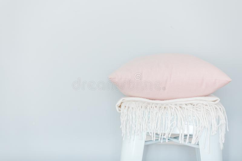 Minimalistic skandinavian picture of a light pink pillow and a white plaid on the chair near a pale blue wall stock images