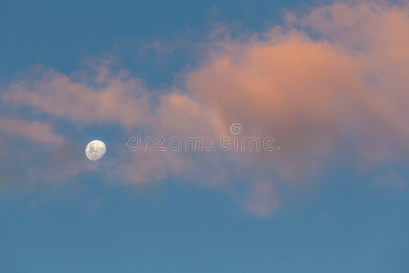 Minimalistic skyscape - φεγγάρι, ουρανός και σύννεφα που καίγονται στο πορτοκαλί φως ηλιοβασιλέματος στοκ εικόνες