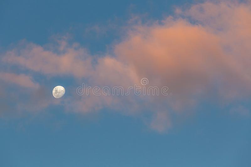 Minimalistic skyscape - moon, sky and clouds glowing in orange sunset light. stock images
