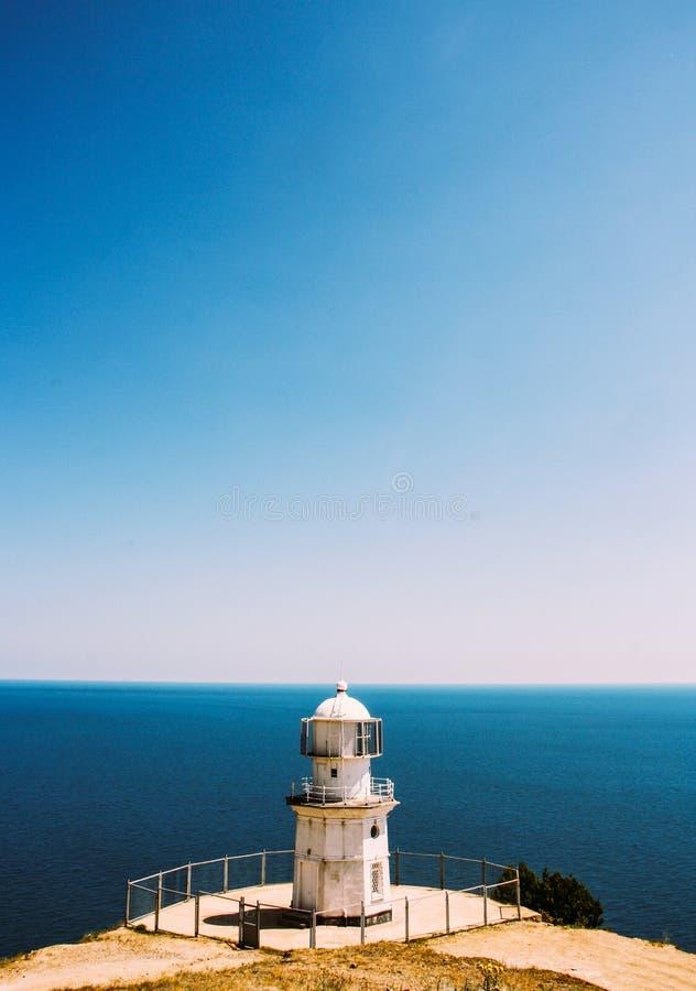 Minimalistic sommarlandskap med fyren och havet royaltyfri fotografi