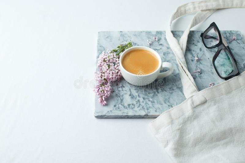 Minimalistic still life with coffee and lilac branches on marble plate and the white table, morning female concept, copy space.  royalty free stock photo