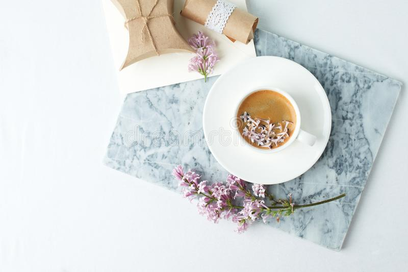 Minimalistic still life with coffee and lilac branches on marble plate and the white table, morning female concept, copy space.  royalty free stock image