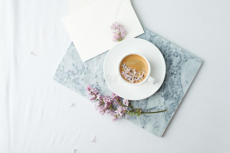 Minimalistic still life with coffee and lilac branches on marble plate and the white table, morning female concept, copy space.  royalty free stock photos