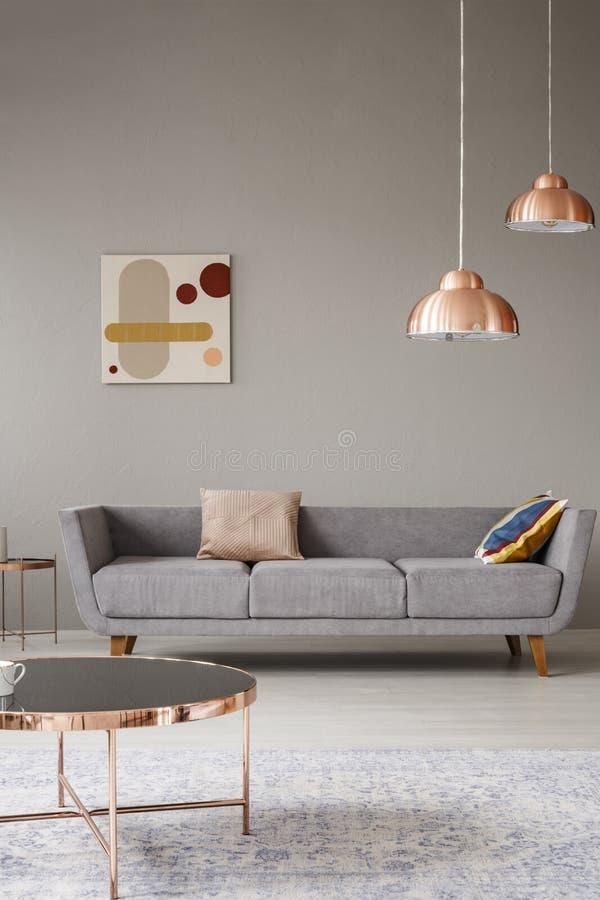 Minimalistic vardagsruminre med en soffa, en koppartabell och en ljuskrona royaltyfri foto