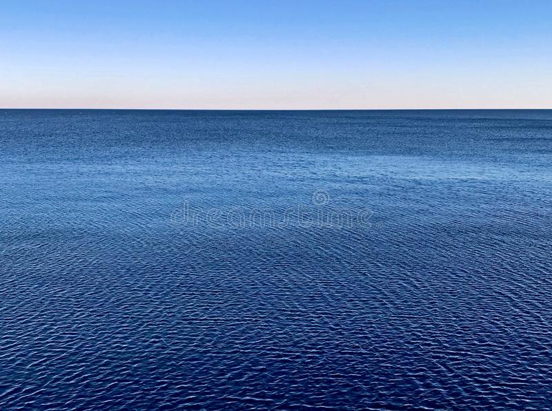 Minimalistic vattenyttersida med den blåa seascapehorisonten och klar lutninghimmel arkivfoton