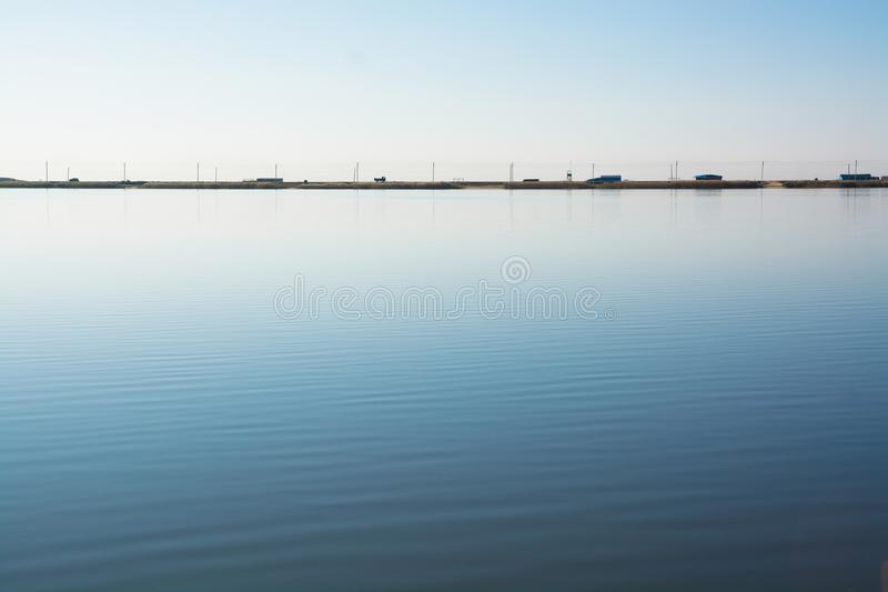 Minimalistic water landscape with road on the lake shore. stock photo