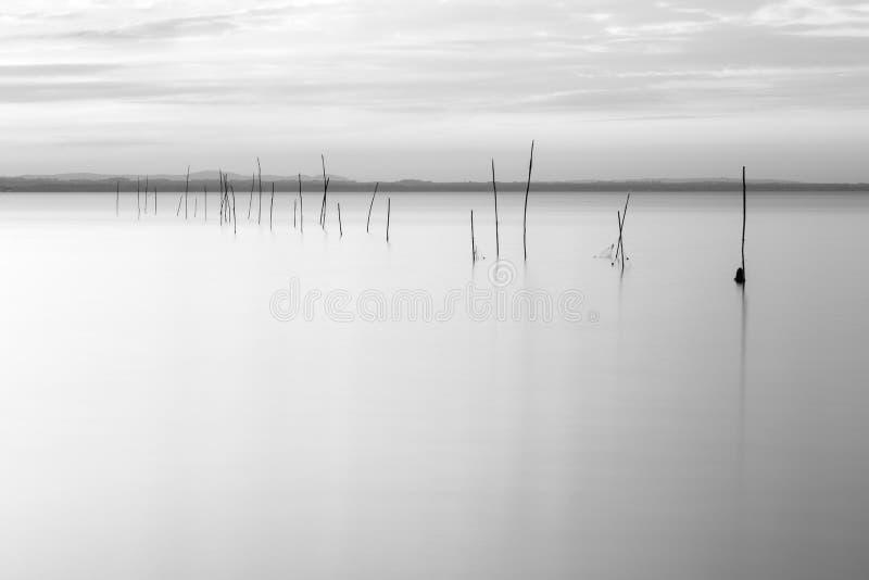 Minimalistic widok Trasimeno jezioro z miękkim światłem, brzmienia, sieci rybackie, słupy i woda, doskonale wciąż zdjęcia stock