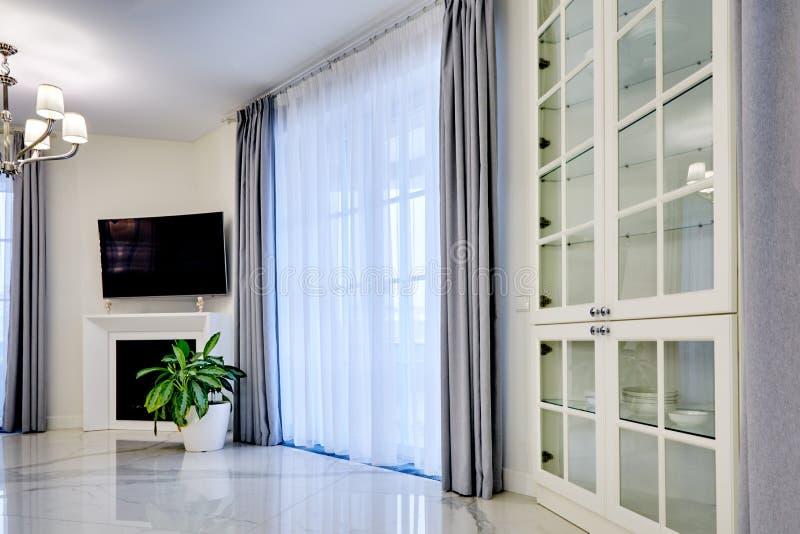 Minimalistic wnętrze żywy pokój w lekkim brzmieniu z marmurową podłogą, wielkimi okno i grabą pod TV, obrazy stock