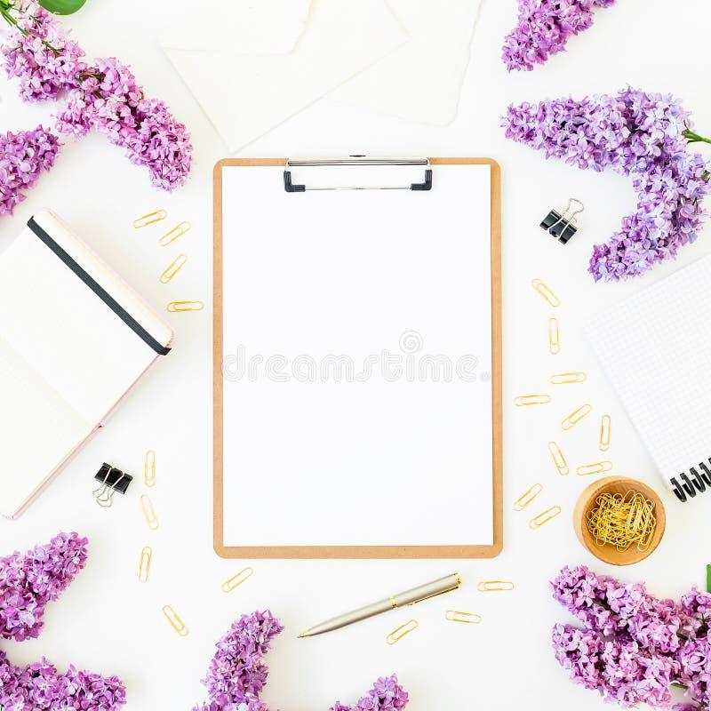 Minimalistic workspace biurko z schowkiem, notatnikiem, piórem, bzem i akcesoriami na białym tle, Mieszkanie nieatutowy, odgórny  zdjęcie stock