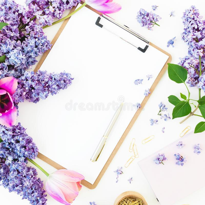 Minimalistic workspace with clipboard, envelope, pen, lilac, petels and accessories on white background. Flat lay, top view. Beaut. Minimalistic workspace with stock photography