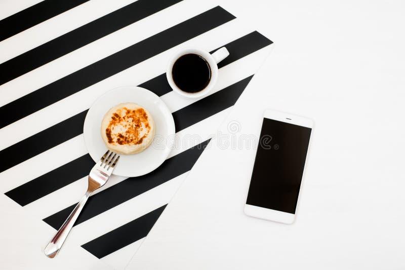 Minimalistic workspace med smartphoneåtlöje upp, kopp kaffe, bageri på randig svartvit bakgrund lekmanna- stil för lägenhet fotografering för bildbyråer