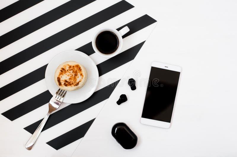 Minimalistic workspace med smartphoneåtlöje upp, koppen kaffe, trådlös earphoneson gjorde randig svartvit bakgrund Lekmanna- läge royaltyfri bild