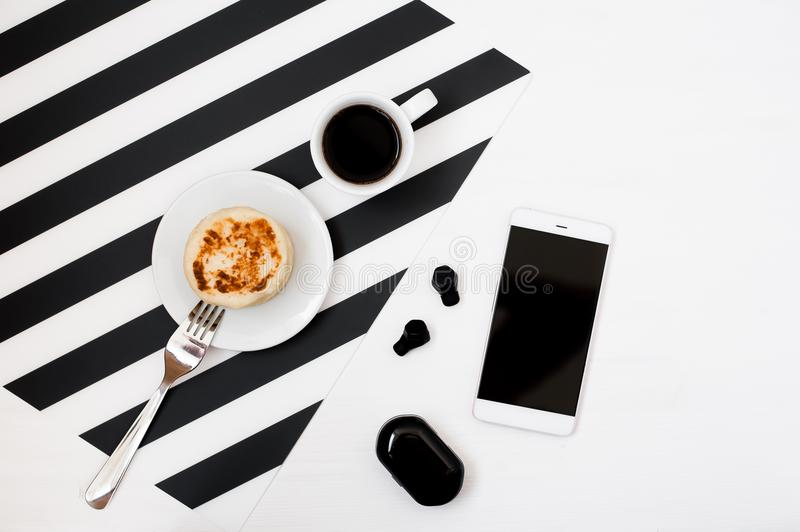 Minimalistic workspace with smartphone mock up, cup of coffee, wireless earphoneson striped black and white background. Flat lay royalty free stock image
