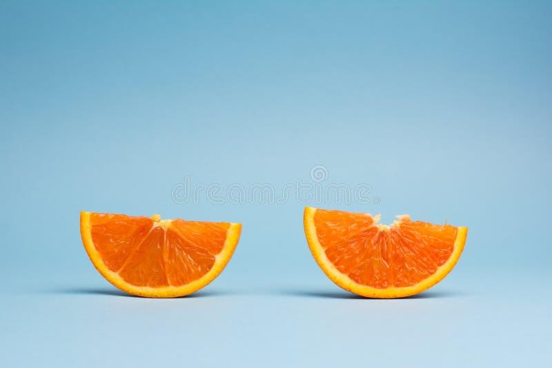 Minimalistic wystrzału sztuki koloru pojęcie: dwa plasterka pomarańczowa owoc na błękitnym tle zdjęcie royalty free