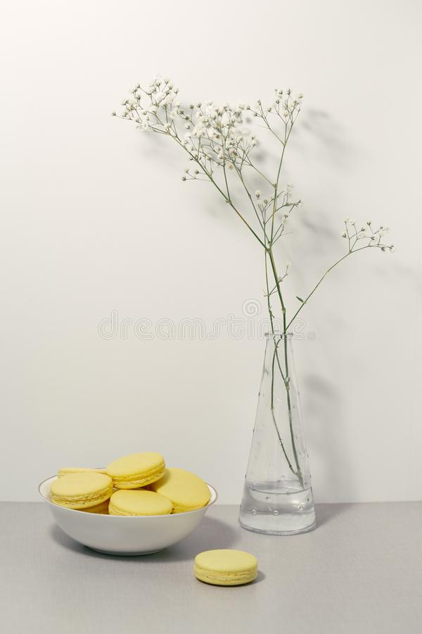 Minimalistic yellow macarons in white dish on table. Vase with flowers stock photo