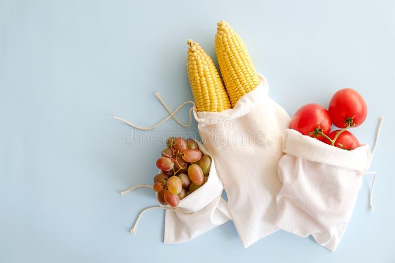 Minimalistic-Zusammensetzungen mit Bündel verschiedenen Obst und Gemüse im recyclebaren Schnursack lizenzfreie stockbilder