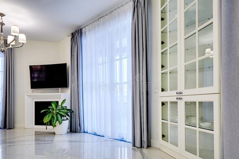 Minimalisticbinnenland van woonkamer in lichte toon met marmeren bevloering, grote vensters en open haard onder TV stock afbeeldingen