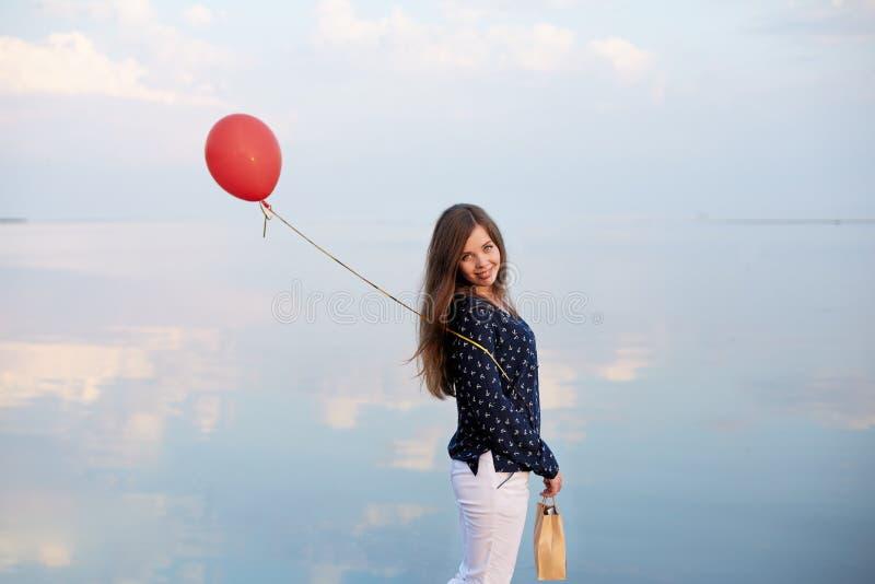 Minimalisticportret van jonge vrouw met rode luchtballon en huidige zak dichtbij de kalme overzeese of meerkust Wolken stock afbeelding