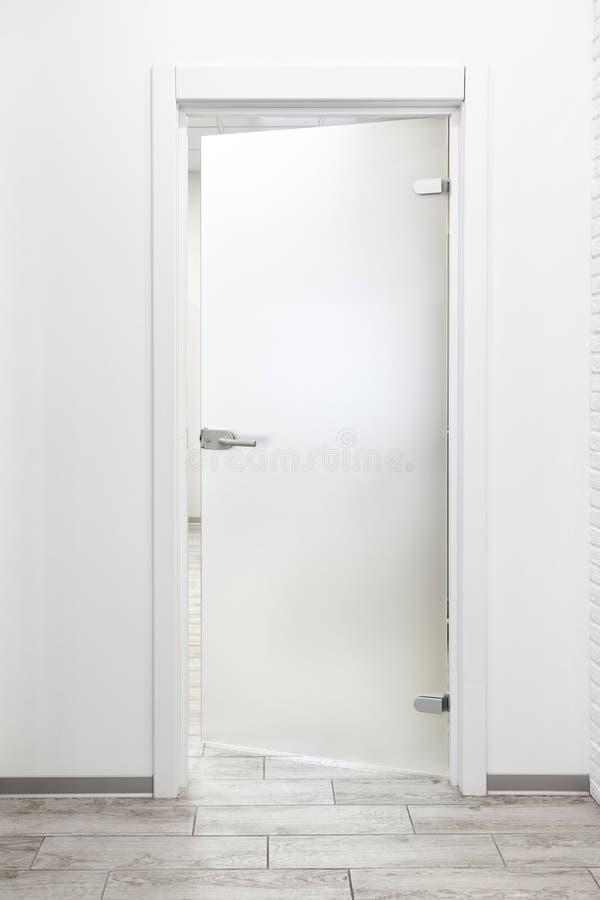 Minimalistisch wit bureaubinnenland met berijpte op een kier glasdeur royalty-vrije stock afbeeldingen