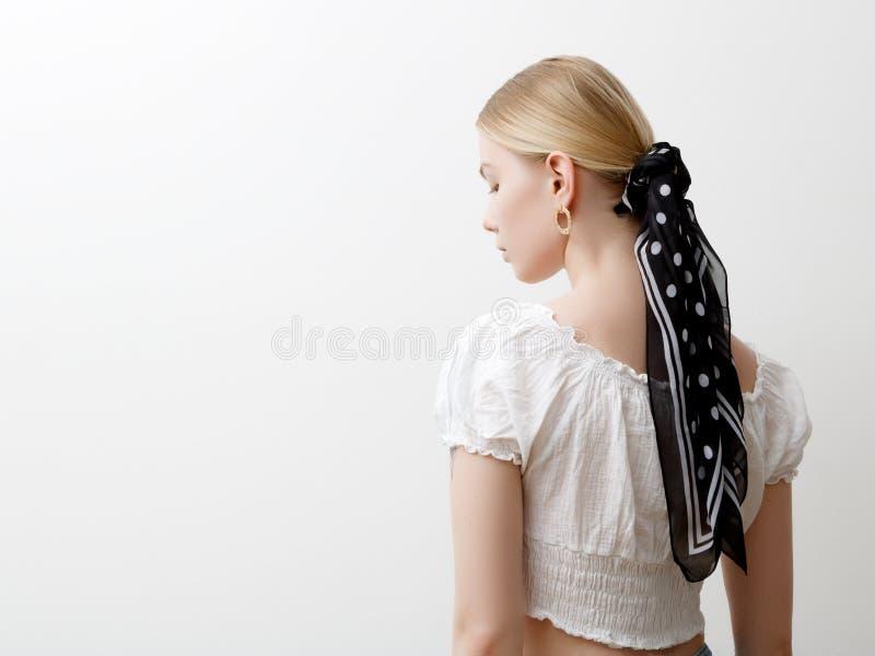 Minimalistische foto, Modieus meisje in modieuze de zomerdingen Mening van de rug Oorringen, een ring, een sjaal op haar hoofd royalty-vrije stock afbeelding