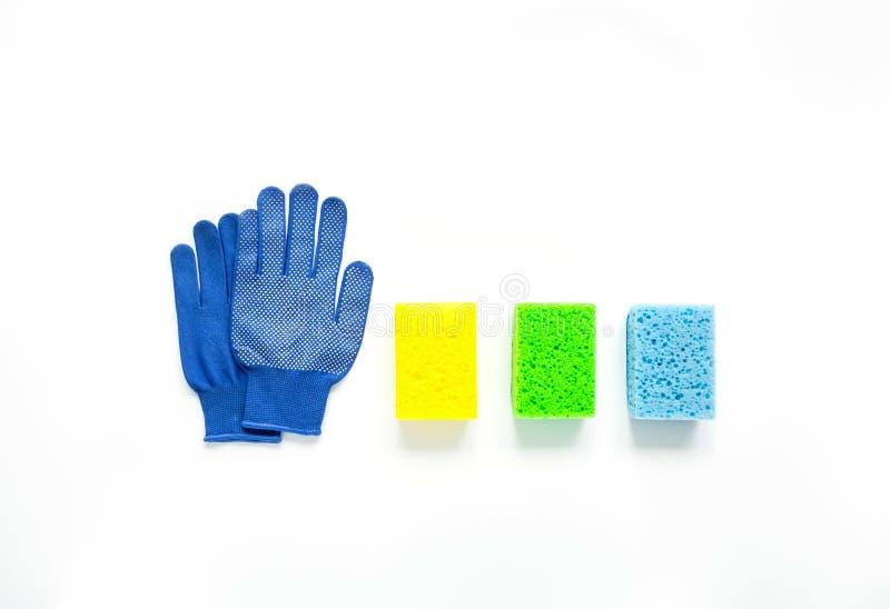 Minimalistische het schoonmaken samenstelling op witte achtergrond Stoffenhandschoenen en kleurrijke sponsen Vlak leg stock afbeelding