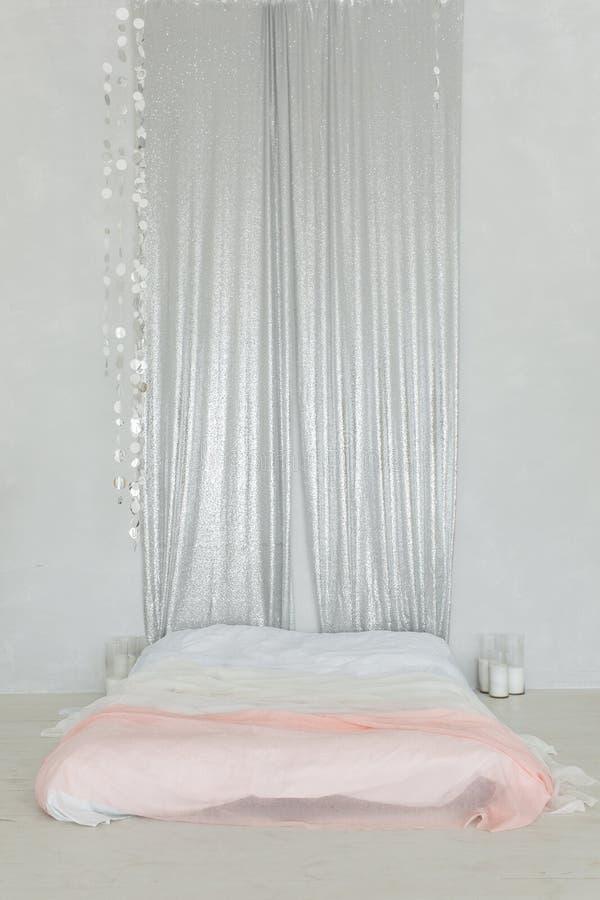 Minimalistische slaapkamer met erachter tweepersoonsbed op vloer en zilveren gordijn Verticaal schot stock foto's