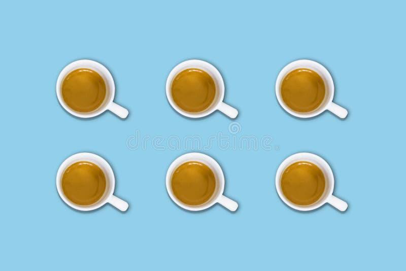 Minimalisty wzór z odgórnym widokiem grupa filiżanki na bławym pastelu stole obrazy royalty free