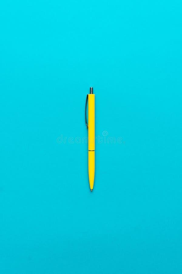 Minimalistycznego mieszkania nieatutowa fotografia żółty ballpoint pióro nad turkusowego błękita tłem zdjęcie stock
