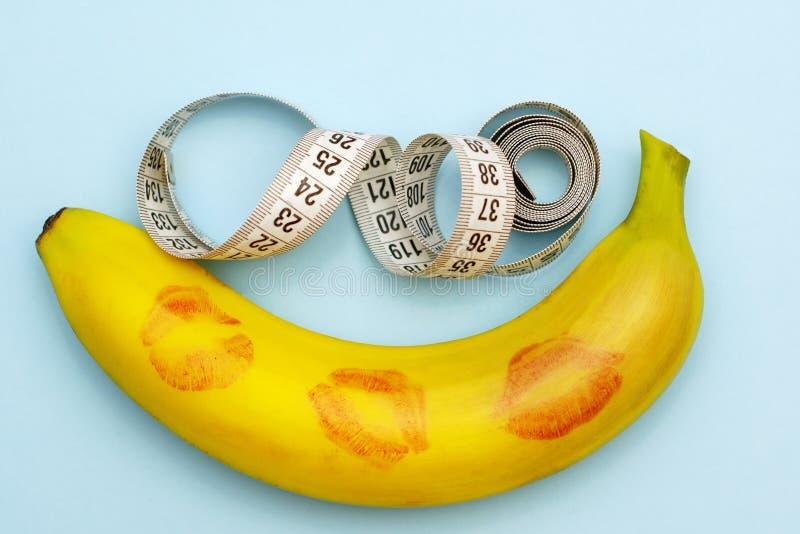 Minimalizm, banan w pomadce od całowania obok pomiarowej taśmy, rozmiar liczy się obrazy royalty free