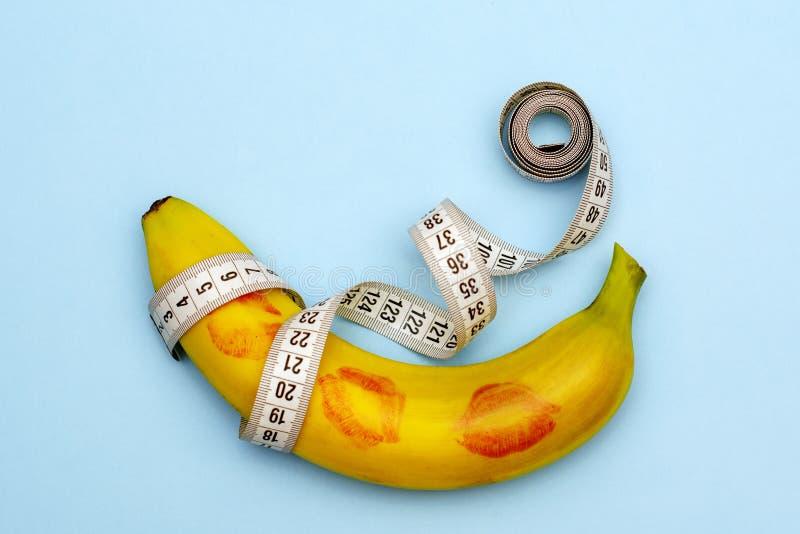 Minimalizm, banan w pomadce od całowania obok pomiarowej taśmy, rozmiar liczy się zdjęcia stock
