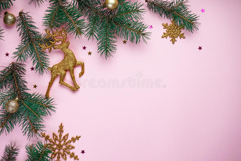 Christmas composition. Christmas tree branches, with New Year`s gold ornaments and multi-colored sweets on a pink background. With place for text, top view stock photos