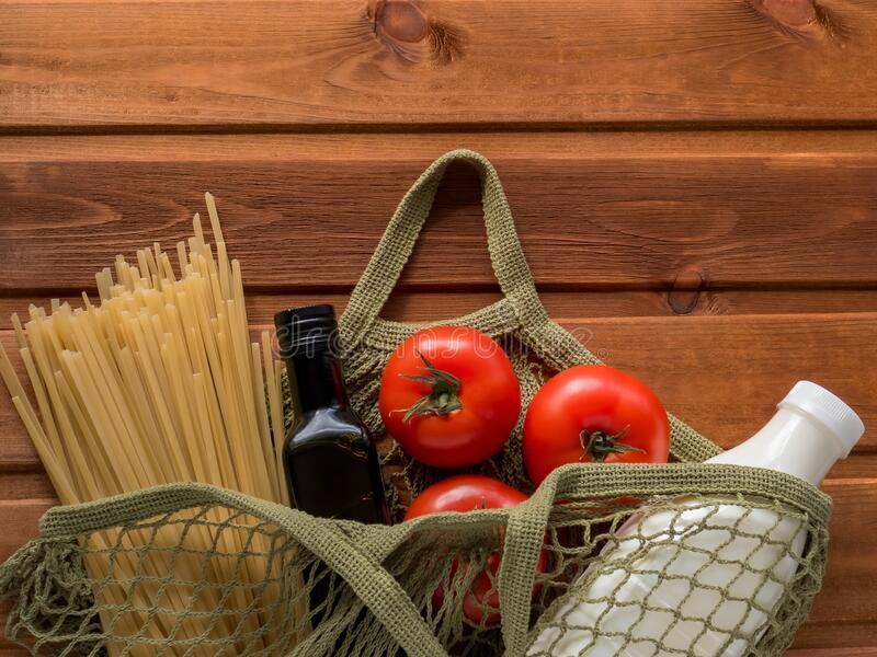 Minimum set of products in cotton mesh bag. Pasta, oil, milk, tomato on wooden background. Increase in produce prices. Pasta, oil, milk, tomato on wooden royalty free stock photography