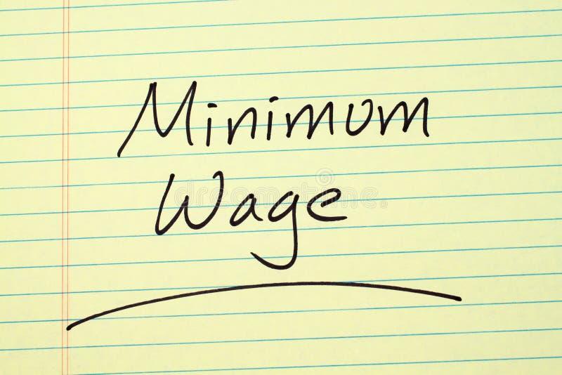 Minimumloon op een Geel Wettelijk Stootkussen stock afbeeldingen