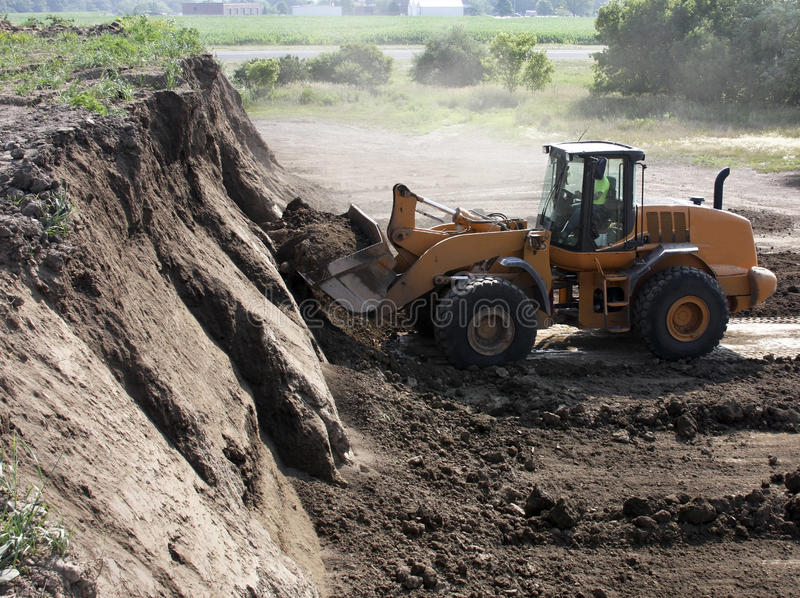 Mining dirt. Heavy equipment operator mining dirt from a hill stock photography