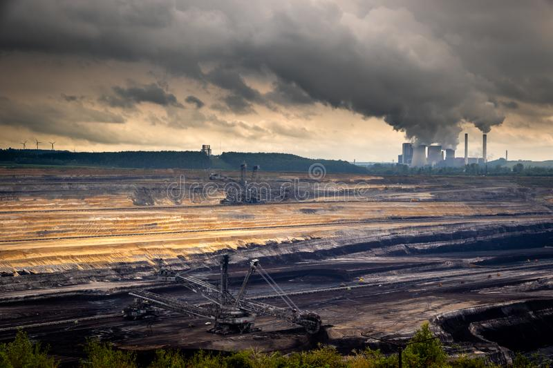 Mining equipment in a brown coal open-pit mine and a power plant with emission stock images
