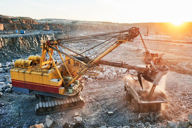 Mining. excavator loading granite or ore into dump truck stock photography